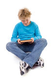 Seated boy looking at book stock image