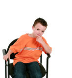 Seated boy in orange shirt Royalty Free Stock Images