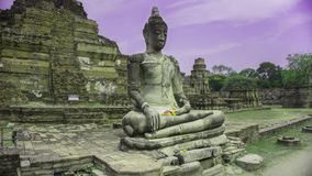 Seated Buddha in Ayutthaya. Seated Buddha statue in the temple named Wat Mahathat, Ayutthaya, Thailand. Ruined pagoda is located behind the Buddha Stock Images