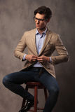 Seated business man buttoning his suit and looks to side Stock Photography