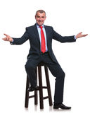 Seated business man welcomes you Stock Photos