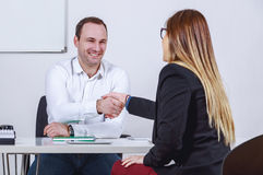 Seated businessmen and businesswoman shaking hands. Seated businessmen and businesswoman in office shaking hands Royalty Free Stock Photography