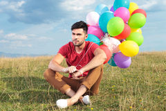 Seated casual man with balloons looks away Stock Photo