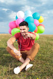 Seated casual man with balloons points at you Stock Photography