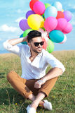 Seated casual man with balloons scratches head Stock Photography