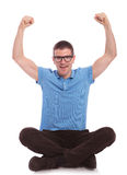 Seated casual man cheers with hands in air Stock Photos