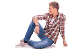 Seated casual man looking to side. Young casual man posing on the floor and smiling while looking to his side, against white background Royalty Free Stock Image