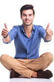 Seated casual man making the ok thumbs up gesture Stock Photo