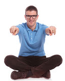 Seated casual man points with both fingers at you Royalty Free Stock Images