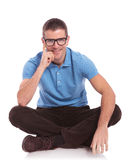Seated casual man smiles with hand on cheek Royalty Free Stock Photo