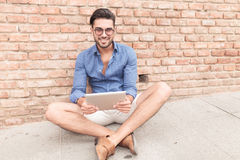 Seated casual man with a tablet pad smiling Royalty Free Stock Image