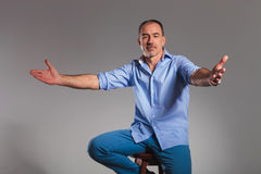 Seated casual man welcoming with open arms Royalty Free Stock Photos