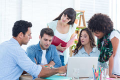 Seated creative business team working on a laptop Royalty Free Stock Images