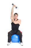 Seated Dumbbell One Arm Triceps Extensions. Young man doing Seated Dumbbell One Arm Triceps Extensions on Fitnes Ball, phase 2 of 2 Royalty Free Stock Photo