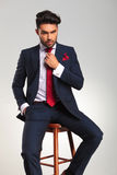 Seated elegant business man fixing his tie Stock Photo