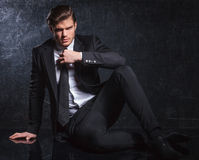 Seated fashion man is fixing his black tie Stock Photo