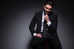 Seated fashion man smiles at you. Portrait of a seated young fashion man smiling for the camera while touching his beard. on a dark background Stock Photo