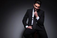 Seated fashion man smiles at you Stock Photo