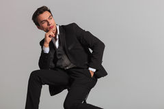 Seated fashion model in tuxedo looks back over his shoulder Stock Images