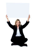 Seated female employee holding white clipboard over her head Royalty Free Stock Images