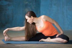 Seated Floor Hamstring Stretch. Beautiful young woman dressed in bright sportswear enjoying yoga indoors. Yogi girl working out in grunge interior with blue wall royalty free stock image