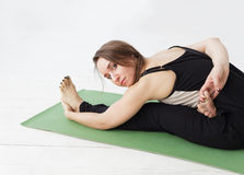 Seated forward bend. Intense dorsal stretch girl is doing yoga while holding a difficult asana Royalty Free Stock Photo