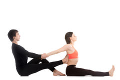 Seated forward bend pose with partner Stock Photo