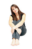 Seated girl. The girl hugged her knees and sitting on the floor Royalty Free Stock Photo
