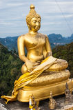 Seated golden Buddha statue on hilltop. Seated golden Buddha statue at hilltop temple  in Krabi, Thailand. Photo taken July 5, 2013 Royalty Free Stock Photography