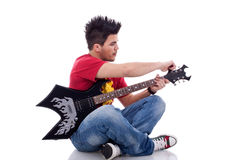 Seated guitarist calibrating his guitar Royalty Free Stock Photography