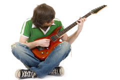 Seated guitarist playing an electric guitar Royalty Free Stock Image
