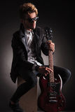 Seated guitarist poses for the camera royalty free stock image