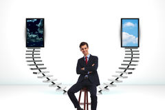 Seated happy business man in front of a big decision. With 3d ladder in the back Royalty Free Stock Image