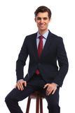 Seated happy business man holding hands on knees. And looks at the camera on white background stock photography