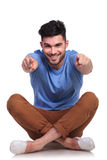 Seated happy casual man pointing fingers Stock Image