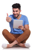 Seated happy  man reading good news on his tablet Royalty Free Stock Photography