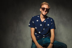 Seated laughing young blond casual man Royalty Free Stock Image