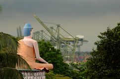 Seated Lotus Buddha views busy seaport Royalty Free Stock Photo