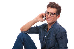 Seated man chats over the phone. Cutout picture of a casual young man sitting on the floor and speakong on the phone while smiling to the camera. isolated on stock image