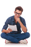 Seated man holds a tablet. Casual young man sitting on the floor with his legs crossed and holding a tablet and rubbing his chin while smiling to the camera Stock Photography