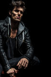 Seated man in leather jacket dreaming away Royalty Free Stock Photo