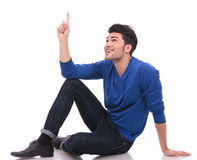 Seated man is pointing at something up Stock Photo