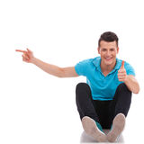 Seated man pointing and thumbs up Royalty Free Stock Images