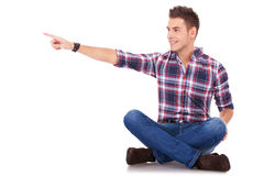 Seated man pointing to his side Royalty Free Stock Photos