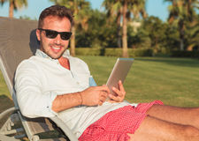 Seated man in sunglasses holding a tablet pad computer Royalty Free Stock Images