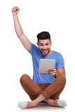 Seated man with tablet pad celebrating success Royalty Free Stock Images
