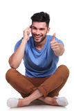 Seated  man talking on  phone and making ok Royalty Free Stock Photography