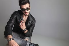Seated man wearing sunglasses and leather jacket looks to side. Seated man wearing sunglasses and leather jacket looks down to side, portrait picture stock images