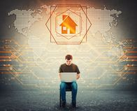 Seated man working on laptop, display digital world map, search on his notebook computer, found a home place as house symbol royalty free stock photography
