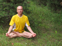 Seated man in yellow in meditation. On a grass Stock Photo